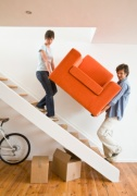 Couple carrying arm chair up stairs